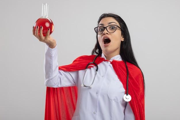 Impressionato giovane superdonna con gli occhiali e lo stetoscopio che solleva la boccetta chimica con liquido rosso fino a guardare la parte anteriore isolata sul muro bianco