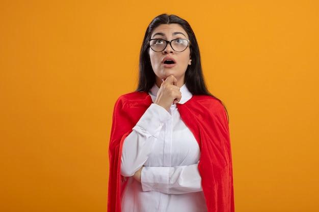 턱을 만지고 안경을 쓰고 감동적인 젊은 슈퍼 우먼은 오렌지 벽에 고립 된 찾고