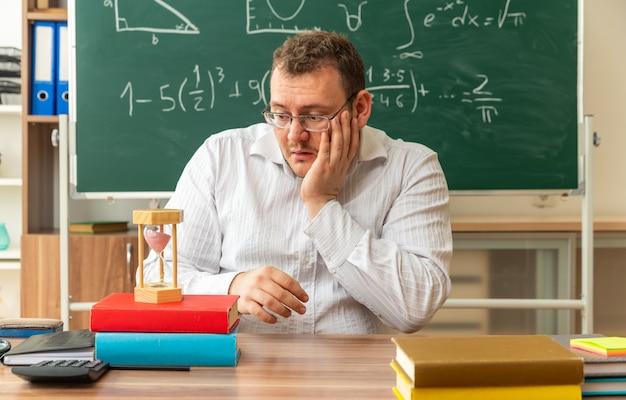 Impressionato il giovane insegnante con gli occhiali seduto alla scrivania con materiale scolastico in classe tenendo la mano sul viso guardando la clessidra