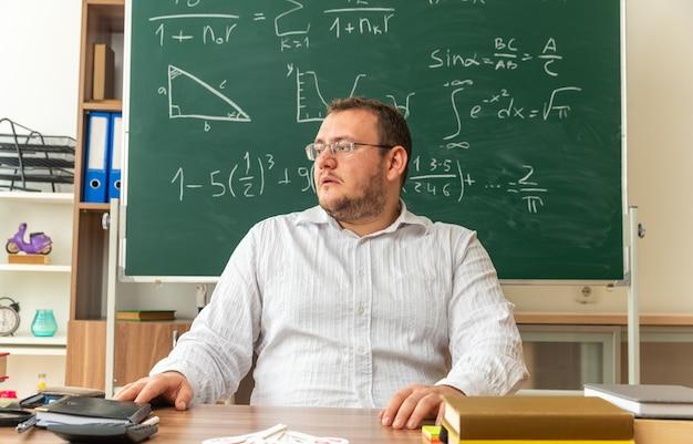 Impressionato il giovane insegnante con gli occhiali seduto alla scrivania con materiale scolastico in classe tenendo le mani sulla scrivania guardando a lato