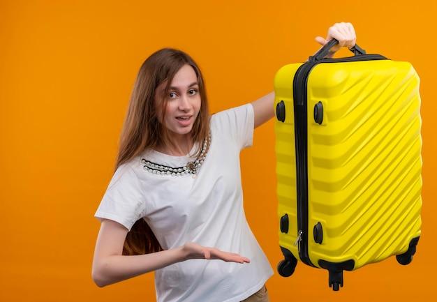 Впечатленная молодая девушка-путешественница поднимает чемодан и показывает на него рукой на изолированном оранжевом пространстве