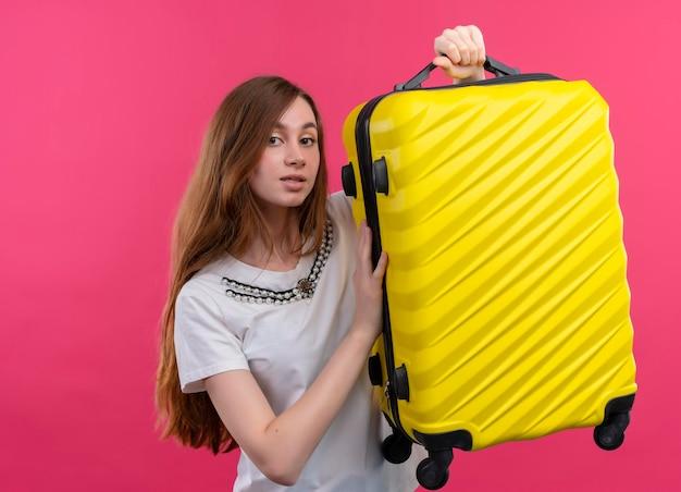 Впечатленная молодая путешественница поднимает чемодан на изолированном розовом пространстве с копией пространства