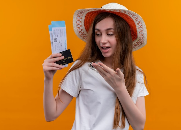 Впечатленная молодая путешественница в шляпе, держащая билеты на самолет, кредитная карта, указывающая на них рукой на изолированном оранжевом пространстве