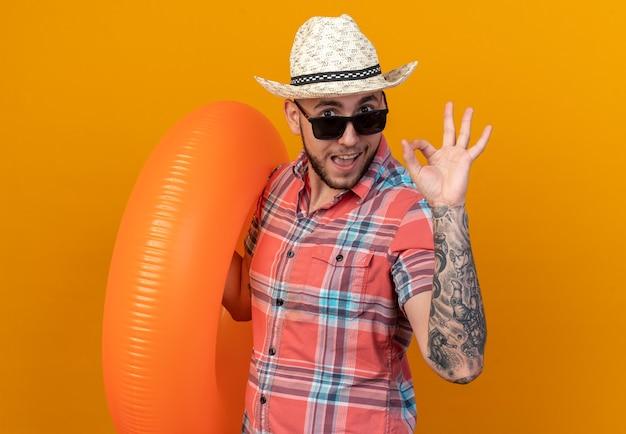 수영 반지를 들고 주황색 벽에 복사 공간이 있는 확인 표시를 하는 태양 안경에 밀짚 해변 모자를 쓴 감동적인 젊은 여행자