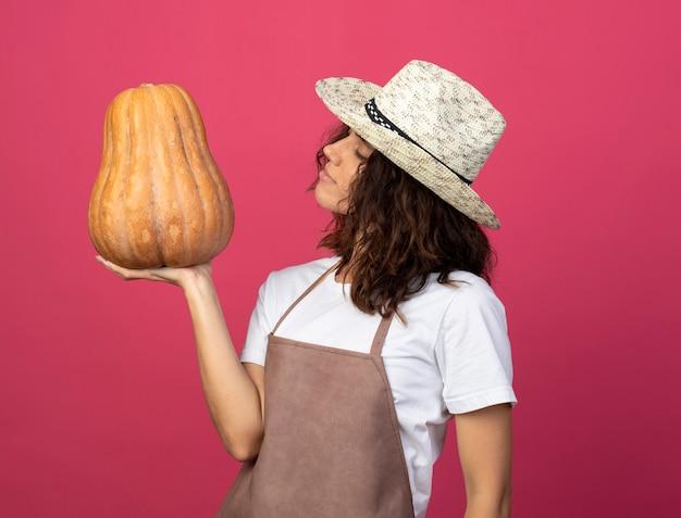 Впечатленная молодая женщина-садовник в униформе в садовой шляпе, держащая и смотрящая на тыкву, изолированную на розовом