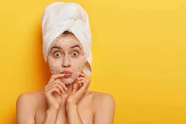 La giovane donna impressionata mantiene le labbra arrotondate, ha gli occhi spalancati, applica uno scrub al sale marino, indossa un asciugamano avvolto sulla testa, ha una pelle morbida e delicata, modella al coperto. persone, spa, peeling, concetto di freschezza