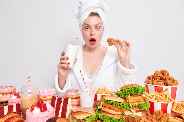 Impressed young woman opens mouth from amazement breaks diet eats junk food