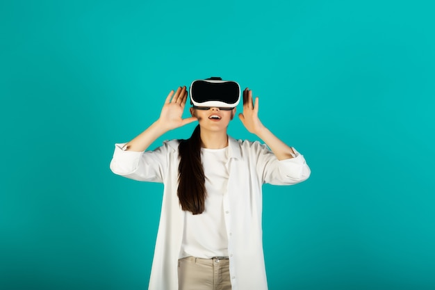 Impressed young woman wearing using virtual reality glasses on blue