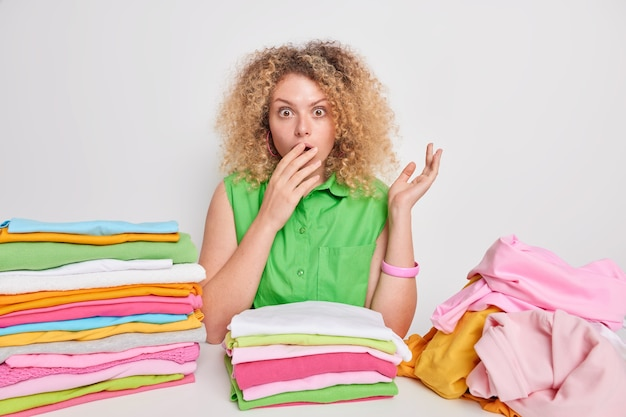 Impressed young woman with shocked expression covers mouth surrounded by folded clothes and pile of unfolded laundry