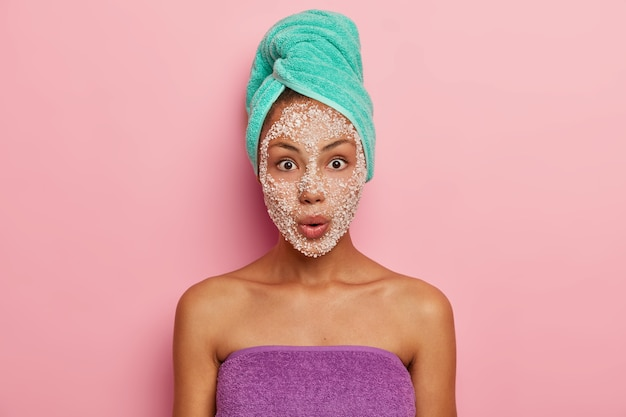 Impressed young woman with shocked expression, has bated breath, eyes popping out, facial sea salt mask for reducing pores