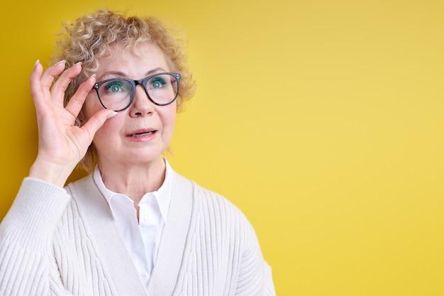 Impressionable elderly woman looking at side fixing eyeglasses