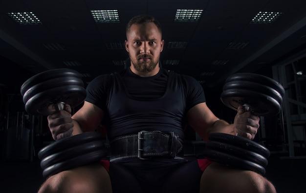 Эффектный спортсмен сидит на скамейке в тренажерном зале с двумя гантелями на ногах