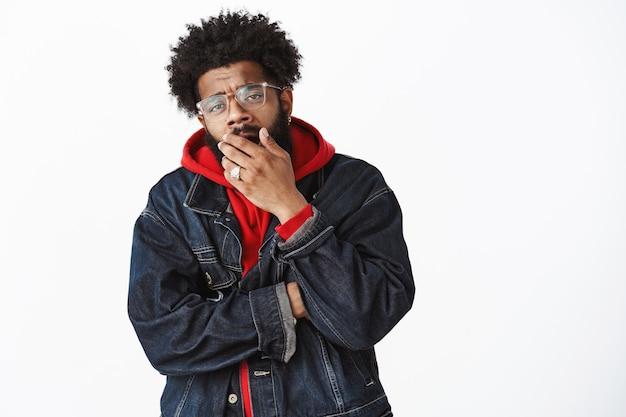 Non impressionante né interessante. ritratto di un uomo afroamericano indifferente che guarda un film noioso con gli occhiali, giacca di jeans sopra una felpa con cappuccio, sbadigliando, coprendosi la bocca con il palmo e sembrando negligente
