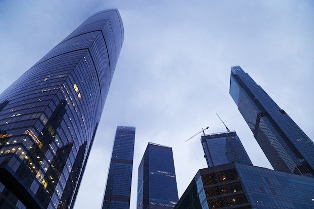 Впечатляющие небоскребы до небес. синее стекло здание из стекла, современный архитектурный стиль. квартиры и офисы в огромных домах.