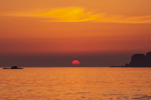 Impressive sunset, big half sun going down to the skyline, at seashore around suwolbong volcano, jeju, south korea.