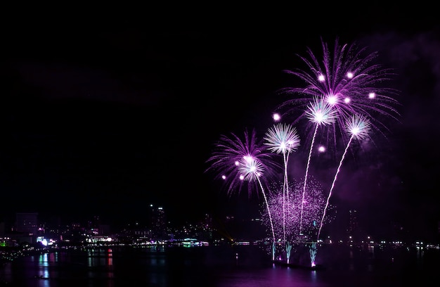 Impressive vivid purple color fireworks splashing in the night sky over the harbor