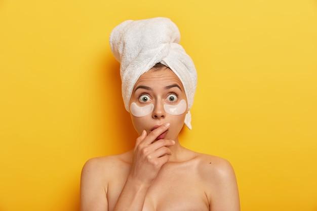 La donna impressionante ha una bellezza naturale, fissa con gli occhi spalancati, applica cerotti di idrogel che fanno la differenza visibile sulla sua pelle, produzione di olio in eccesso, tocca la bocca con le mani