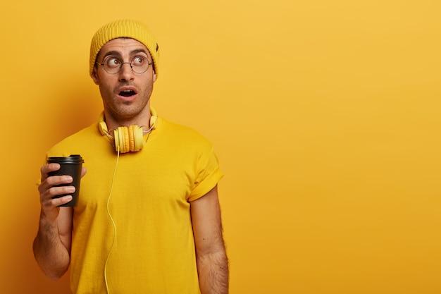 인상적인 젊은이가 말을 잃고 노란색 모자와 캐주얼 티셔츠를 입습니다.