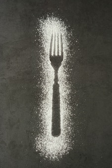 Imprint fork silhouette made of flour on a black background
