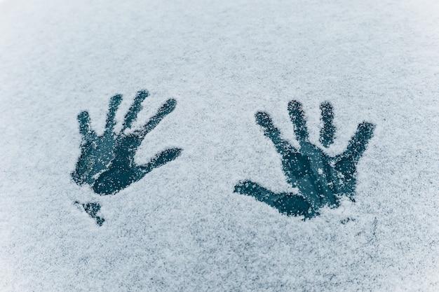 하얀 눈 텍스처에 두 손바닥 손의 인쇄물. 냉동 된 어두운 파란색 유리 배경에 두 인간의 손바닥. 겨울 재미와 추운 날씨 활동의 개념. 눈 텍스처. 소프트 포커스 프리미엄 사진