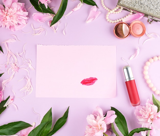 Imprint of red lipstick on an empty pink paper sheet
