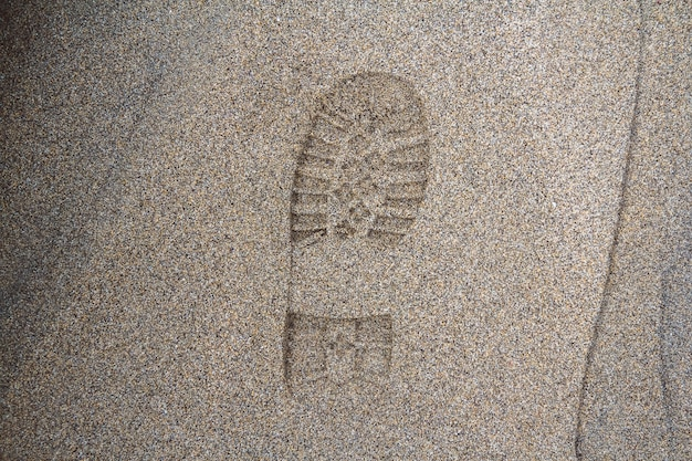 Imprint of the shoe on mud with copy space footprint in the dirt foot step on sand