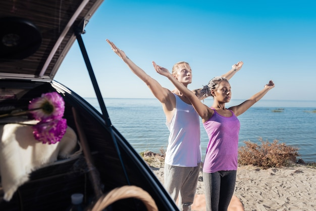柔軟性を改善する。川の近くで一緒に瞑想しながら柔軟性を向上させる健康なカップル