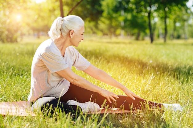 Развивайте свои возможности. веселая пенсионерка улыбается женщина делает спортивные упражнения