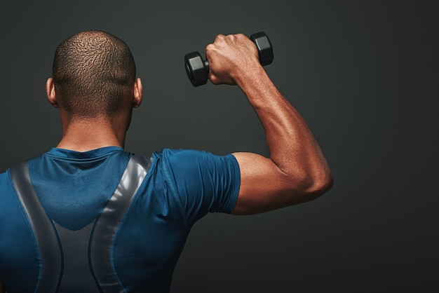 Improve your shape dark skinned sportsman working out with dumbbells over dark background