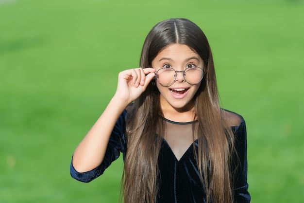 視力の改善が可能です。幸せな子供は眼鏡の緑の草を修正します。視力矯正。メガネとコンタクト。視力検査。小児眼科。眼鏡店。ファッションアイウェア。