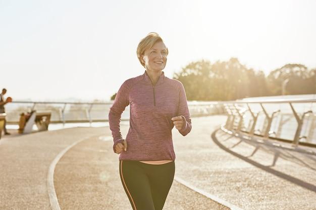 화창한 날 야외에서 달리는 운동복을 입은 행복한 의욕적인 성숙한 여성의 건강 초상화 개선
