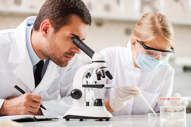 현대 의학을 개선합니다. 실험실에 앉아 실험을 하는 두 젊은 과학자