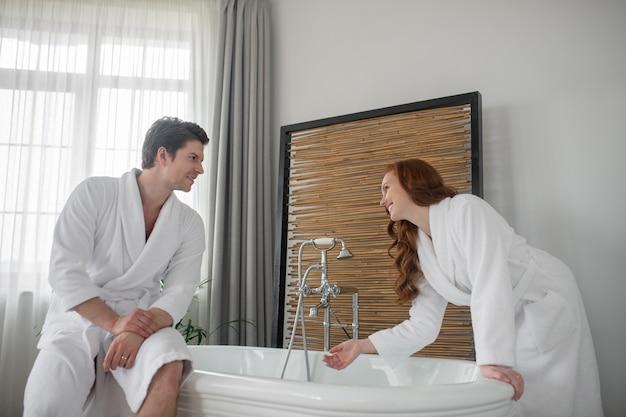 バスルームで。お風呂の準備をしている白いバスローブのカップル