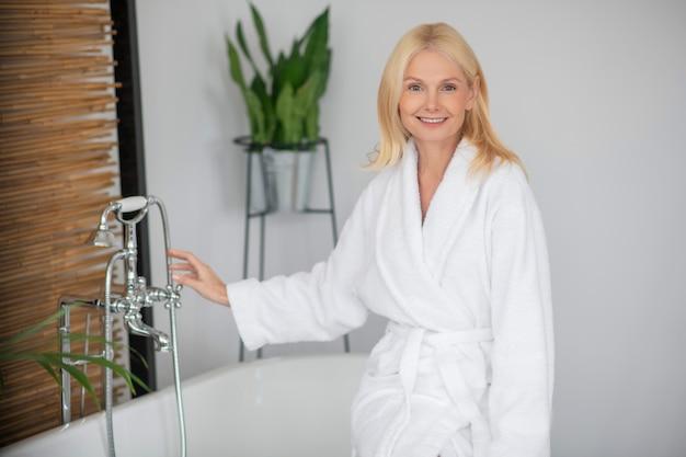 バスルームで。浴室の白いバスローブで金髪のきれいな女性