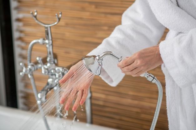 バスルームで。シャワーを保持している白いバスローブの女性のクローズアップ