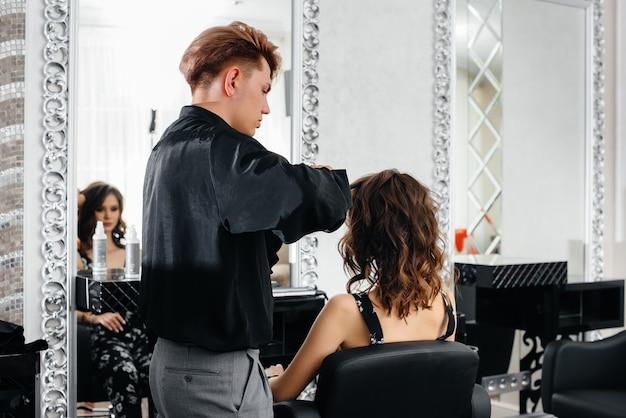 아름답고 현대적인 미용실에서 전문 스타일리스트가 어린 소녀의 이발과 헤어스타일을 만듭니다. 뷰티, 그리고 패션.