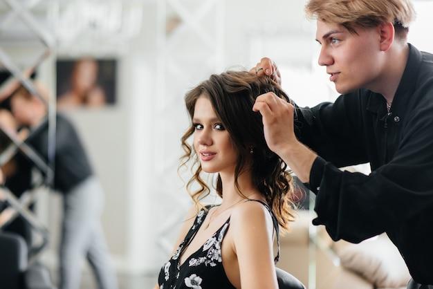 美しくモダンなビューティーサロンでは、プロのスタイリストが若い女の子のためにヘアカットとヘアスタイルを作ります。美しさ、そしてファッション。