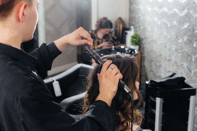 美しくモダンなビューティーサロンで、プロのスタイリストが若い女の子のためにヘアカットとヘアスタイルを作ります