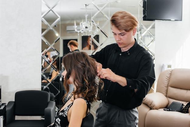 아름답고 현대적인 미용실에서 전문 스타일리스트가 어린 소녀를 위해 이발과 헤어 스타일을 만듭니다.