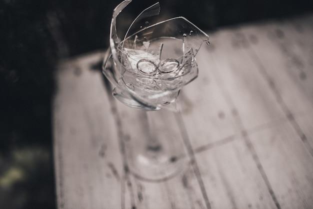 В разбитом хрустальном стекле обручальные кольца жениха и невесты на фоне