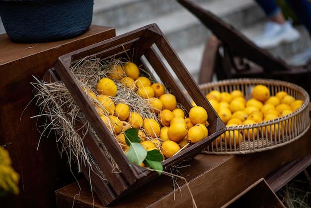 В деревянном ящике коричневого цвета, в соломе - желто-оранжевые лимоны с зелеными веточками. свежий, яркий декор для украшения фестивальной ярмарки. натуральные фруктовые соки. копировать пространство