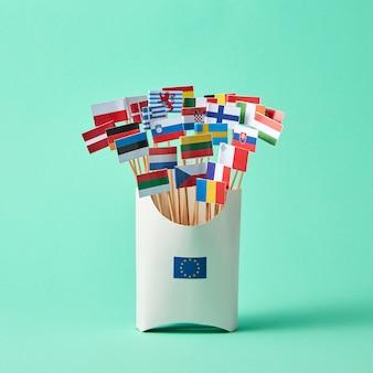 В картонной коробке со знаком европейского союза, коллекция бумажных флагов стран европейского союза на зеленом фоне. экономический, политический союз европейских государств
