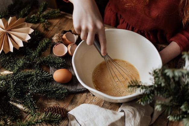セラミックの白いボウルで、ブラウンシュガーと卵を一緒に泡だて器で混ぜます。