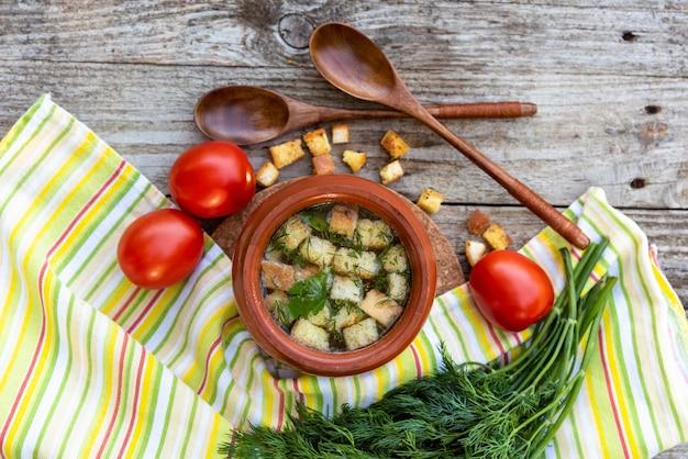 土鍋に、木製のテーブルにクルトンを添えた温かいスープ。