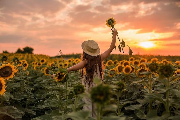 ひまわり畑で、少女が夕日に背を向けて立ち、腕を大きく広げた。