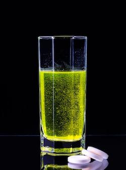 유리 컵에 비타민 c가 들어있는 큰 흰색 정제가 검정색 배경에 물에 용해됩니다.