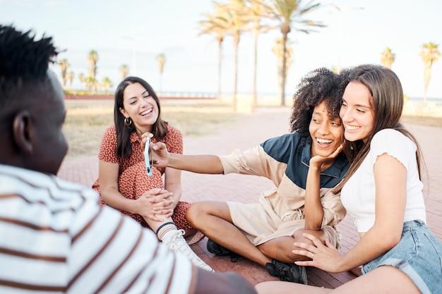 В группе молодых людей две девушки делают селфи на улице у людей, сидящих на полу