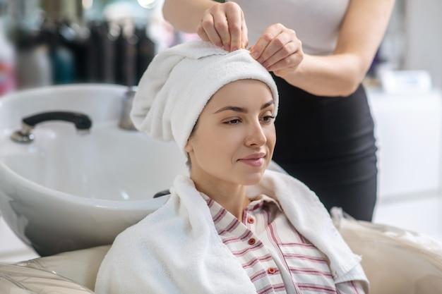 美容院で。クライアントの髪をタオルで乾かすヘアスタイリスト