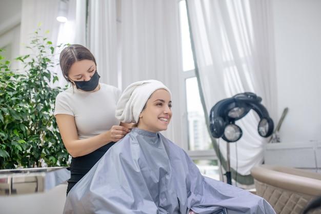 美容院で。顧客の髪をタオルで覆う美容師