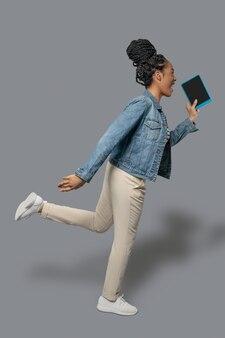 В спешке, спешу. фотография темнокожей молодой женщины, бегущей и держащей планшет